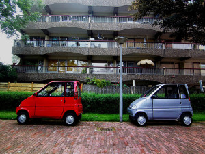 two little cars outside apartment complex, one red