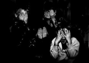 black and white of a group of children covering their eyes