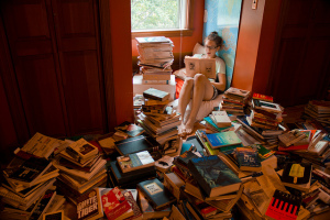 girl sitting in a bright room, surrounded by stacks of books