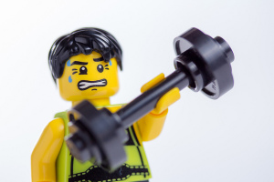 lego man sweating while lifting barbell